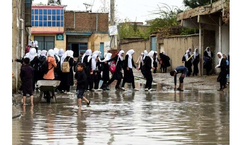 Afghan schoolgirls walk home as heavy rain falls in Kabul