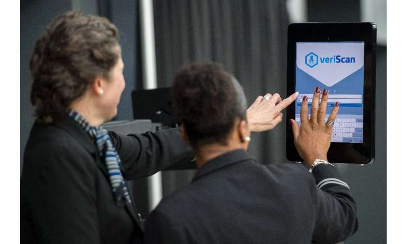 Airline gate agents sign into facial recognition verification system VeriScan at Dulles International Airport