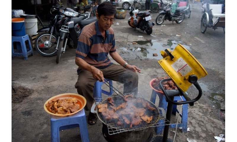 A man grills pork for sale at a market in Phnom Penh, Cambodia, which has banned the import of all pigs and pork products