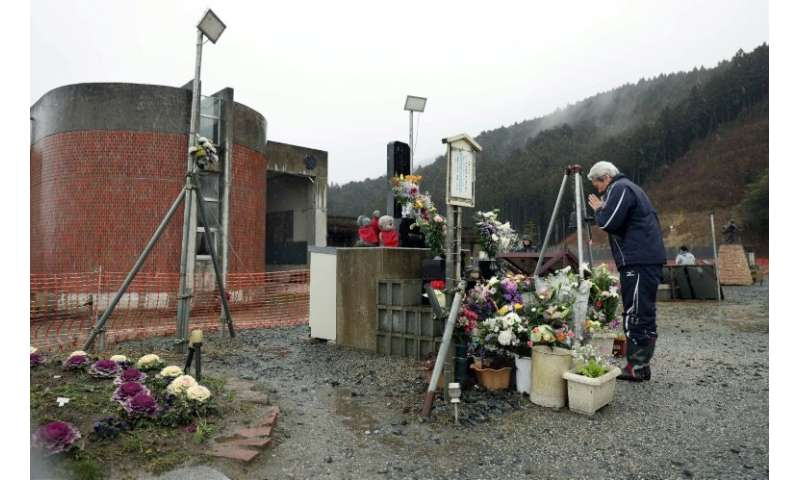 A man prays in front of the former Okawa elementary school in Ishinomaki, Miyagi Prefecture on the eighth anniversary of the 201
