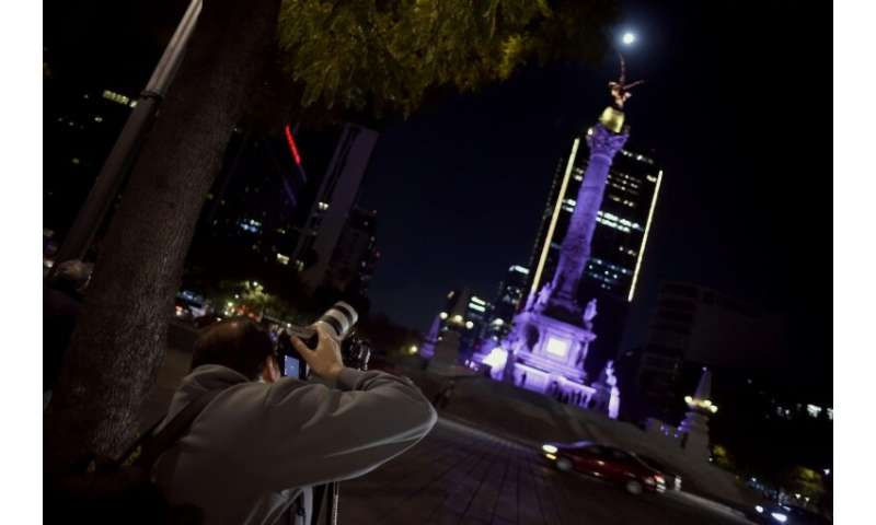 A man taking pictures of the Super Moon during the start of the total lunar eclipse, at the Angel de la Independencia in Mexico