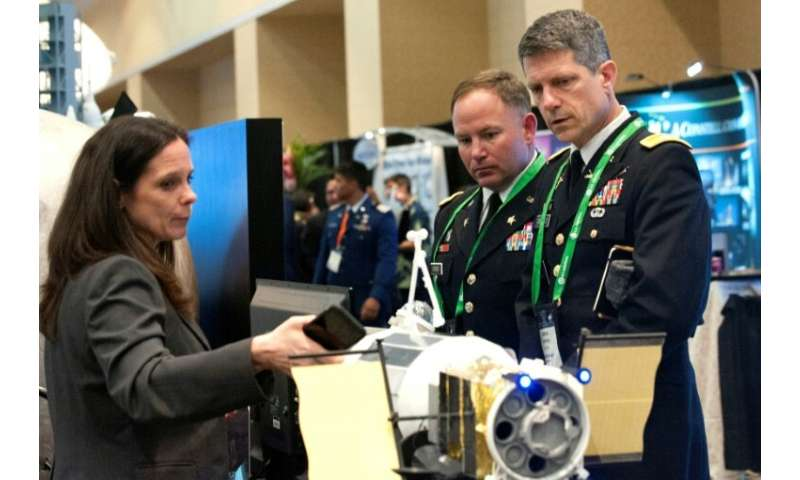 A NASA exhibitor discusses the features of a rocket with members of the US military during the 35th Space Symposium in Colorado,