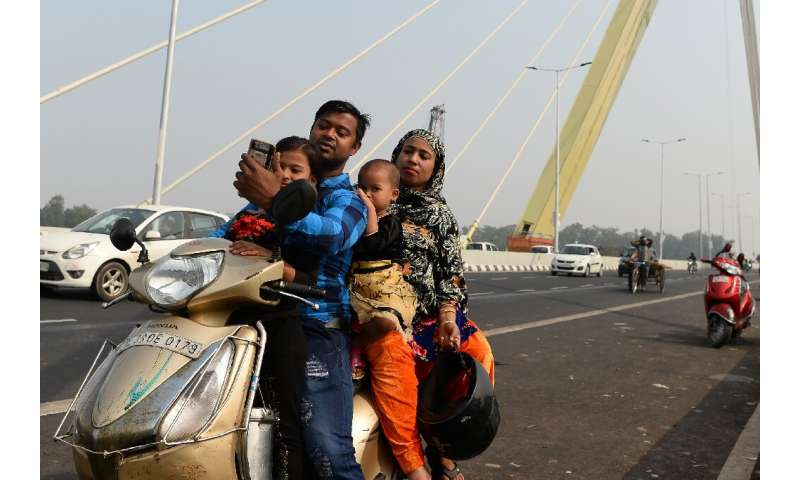An Indian man takes a selfie with his family on a scooter on the newly-built Signature Bridge in New Delhi on November 15, 2018—