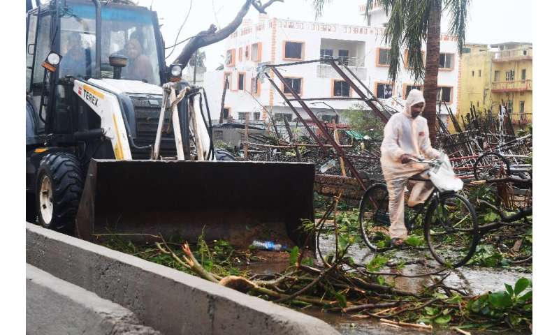 An Indian resident rides a bike past a bulldozer clearing debris from a road in Puri