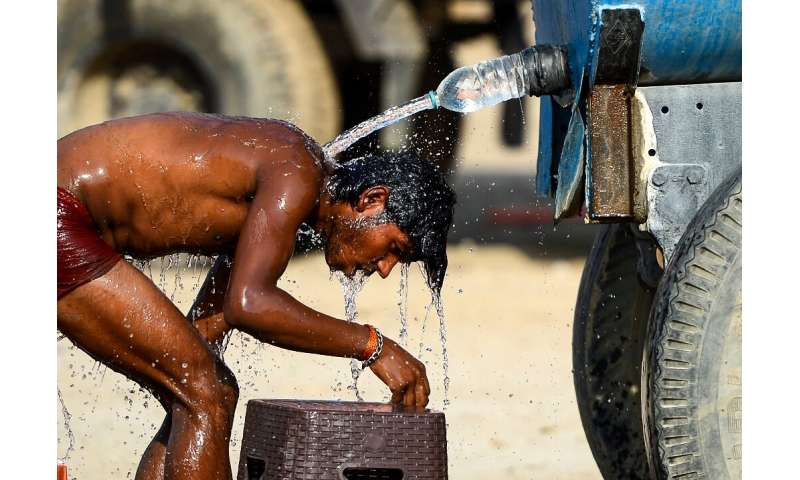 An Indian truck driver takes a cooling bath in Allahabad, where temperatures have neared 50 degrees Celsius (122 Fahrenheit)