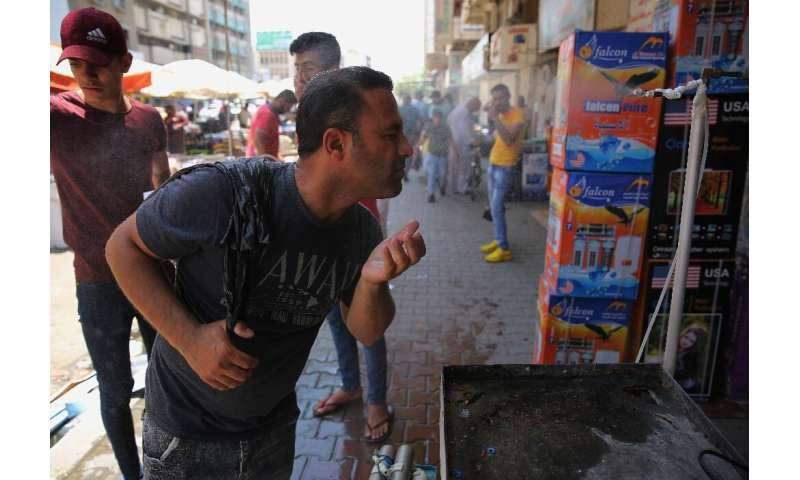 An Iraqi man uses a curbside shower to cool off