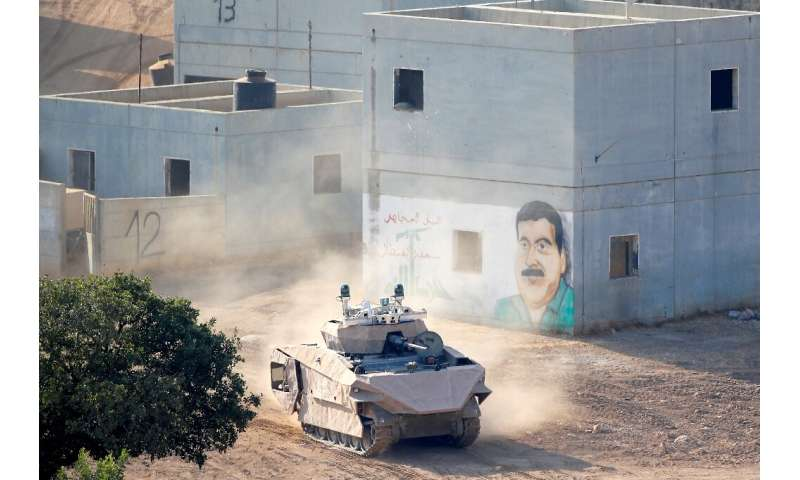 An Israeli tank drives through a mock Arab village used for battle training, at a base in northern Israel