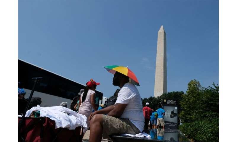 A street hawker wears an umbrella hat to fend off sweltering heat in Washington amid an oppressive heat wave