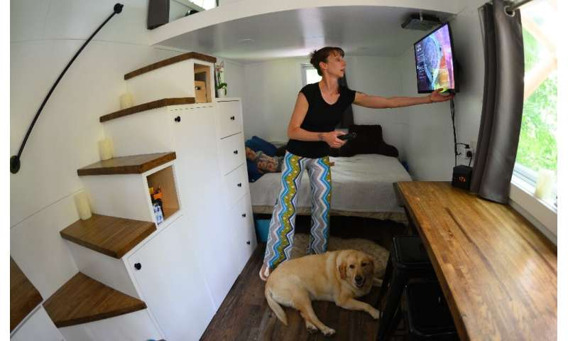 Brandy Jones adjusts the TV set in her tiny home—construction is focused on maximizing all available space