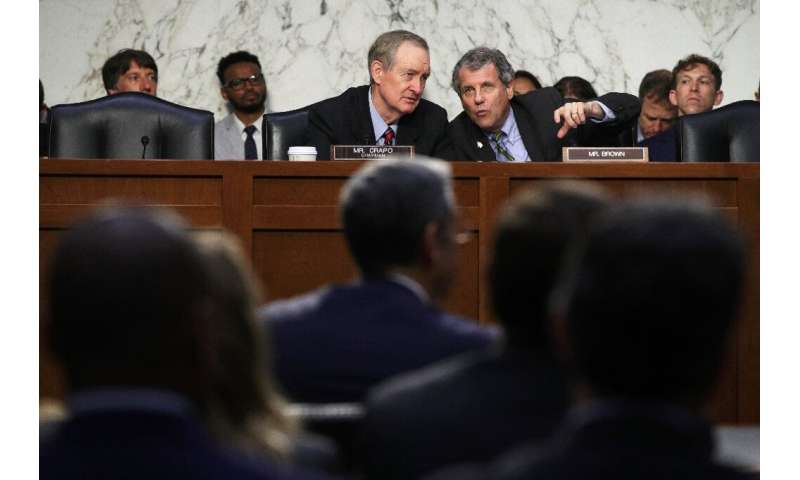 Committee chairman Senator Mike Crapo (C) listens to ranking member Senator Sherrod Brown (R) during a hearing before the Senate