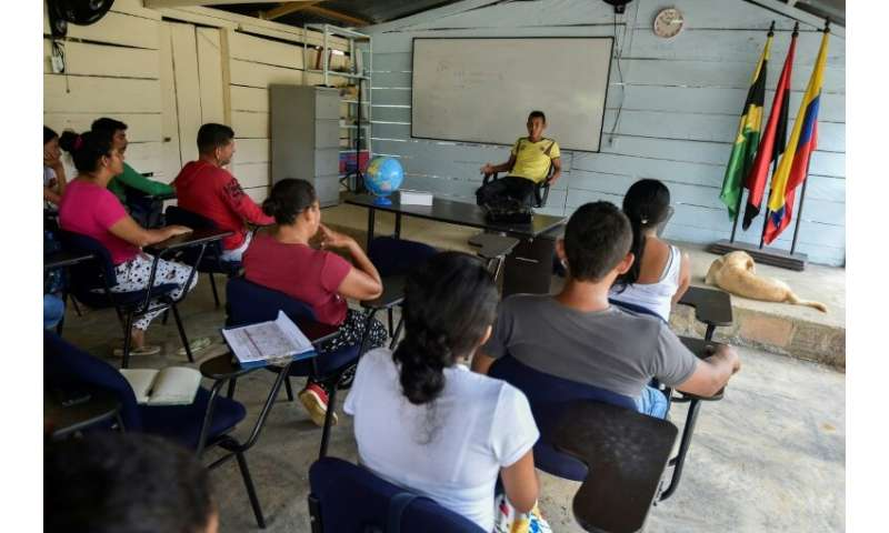 Community leader Alex Molina (C), who accepted the government's crop substitution plan, talks to local farmers at at Puerto Las