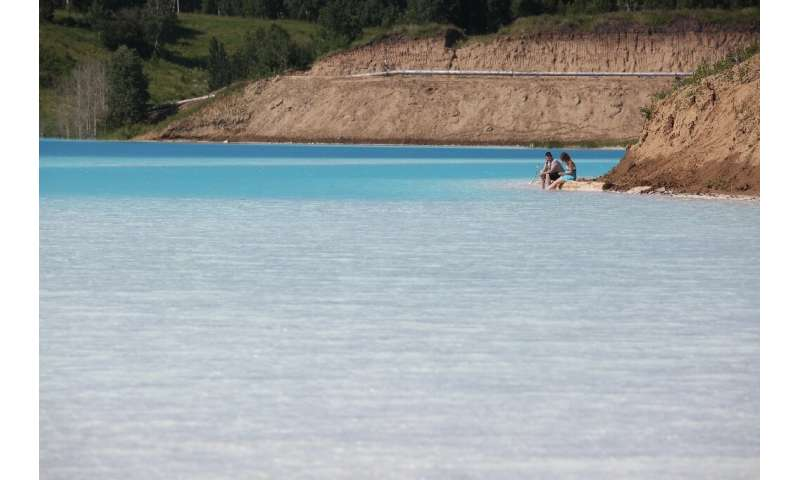 "Despite ""Danger Zone"" signs, a couple risk cooling their feet at the edge of the turquoise lake—but the Siberian Gener"