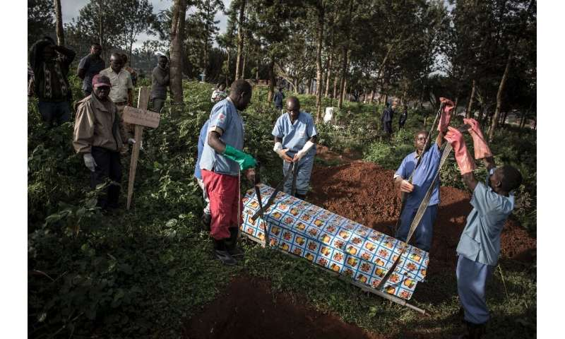 Gloved health workers conduct the burials and keep the loved ones at a safe distance
