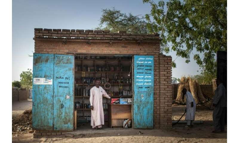 Ibrahim Hassan, 42, a Sudanese trader and refugee from Treguine camp, poses in front of his shop in Hadjer Hadid
