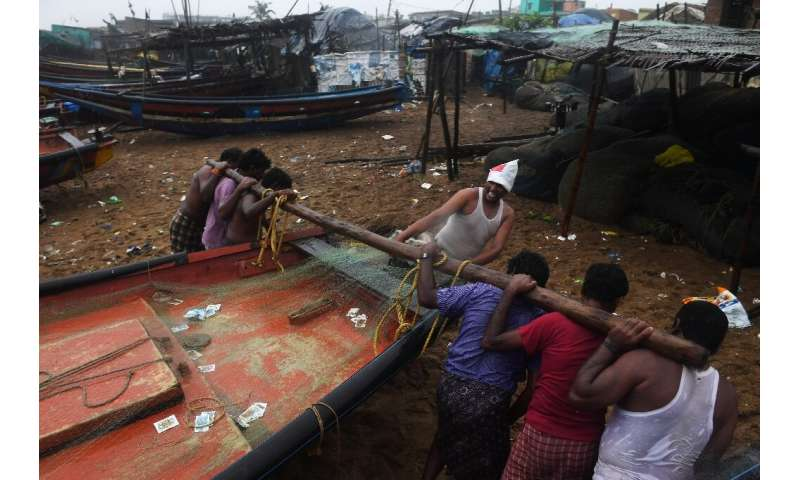 Indian fishermen secure their boats in Puri before Cyclone Fani makes landfall