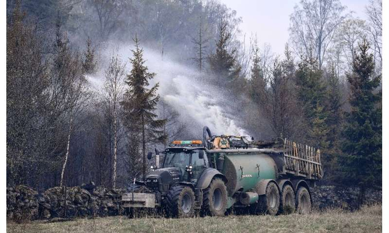 In Sweden, tractors hauling fertilizer tanks filled with water are used to put out a forest fire