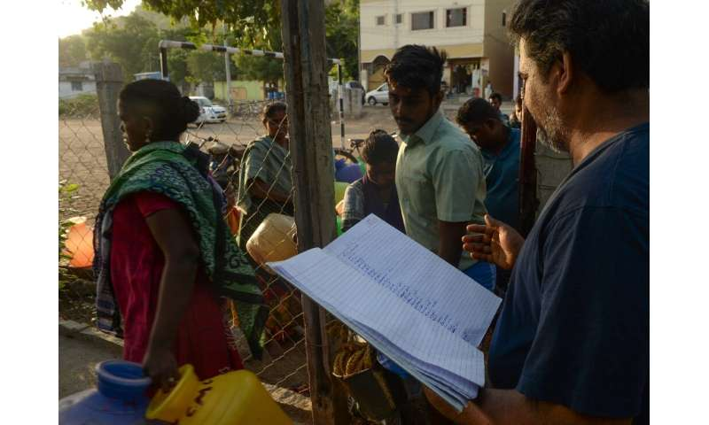 Local officials organise a lottery to determine who gets to the front of the water queue