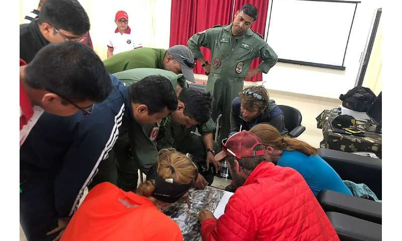 Mountaineers and rescuers study a map of Nanda Devi in an effort to pinpoint the location of the missing climbers on June 3, 201