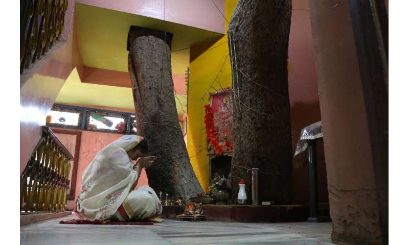 Neelu Kesharwani, daughter-in-law of Moti Lal Kesharwani who built their house around a tree, performs a ritual on the second fl