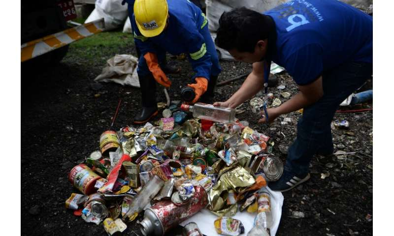 Nepali workers search for recyclable materials from a a pile of waste collected from Mount Everest