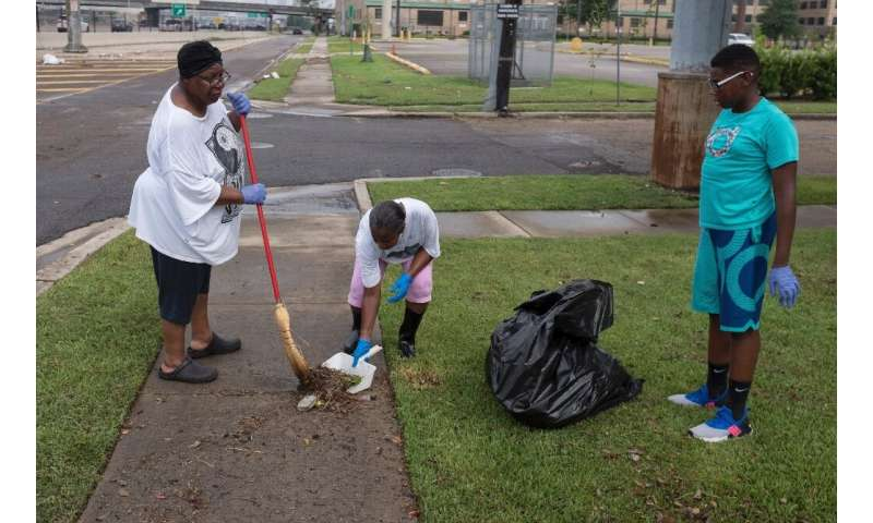 New Orleans residents clean up debris in their yard after flash floods struck the area early on July 10