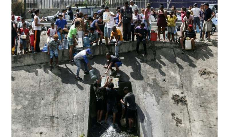 People collect water from a broken pipe flowing into a sewage canal at the Guaire river in Caracas on March 11, 2019