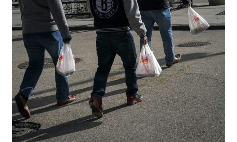 People in New York are seen carrying single-use plastic bags, which would be banned under a new law