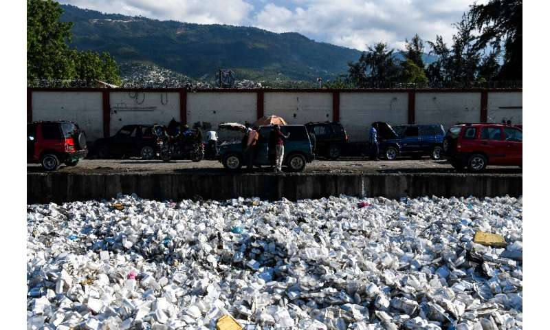 Plastic waste is seen floating on a sewage canal in the Haitian capital Port-au-Prince, on April 23, 2019. Around 180 government