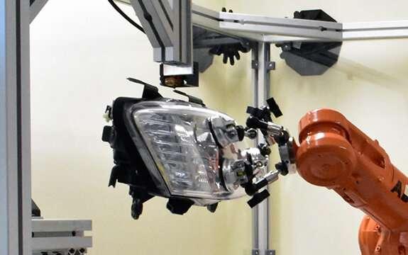 Robot 3-D prints replacement bracket on headlamp