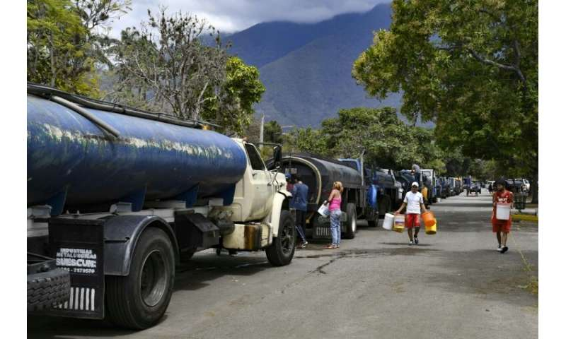 Tanker trucks line up as residents fill drums and buckets with drinking water in Caracas—just another indignity of Venezuela's c