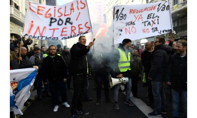 """Taxi drivers hold flares and placards reading """"Regulation now"""" during a demonstration in to protest against online rid"""
