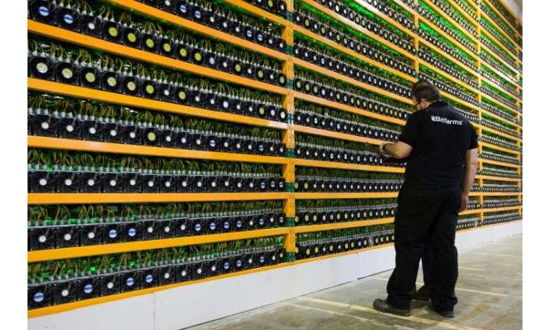 Technicians inspect bitcoin mining at Bitfarms in Saint Hyacinthe, Quebec