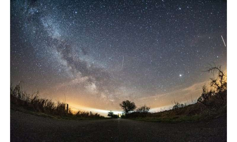The milky way and meteors of the April Lyrids annual meteor shower in the night sky over the Baltic Sea