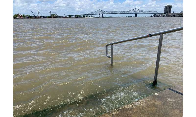 The swollen Mississippi River laps at the stairs on a protective levee in New Orleans