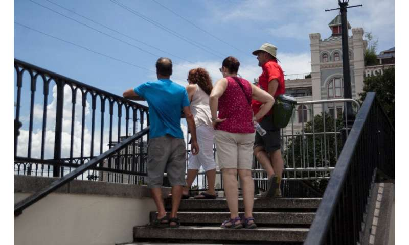 Tourists look out towards the Mississippi River at Artillery Park in New Orleans as Tropical Storm Barry approaches