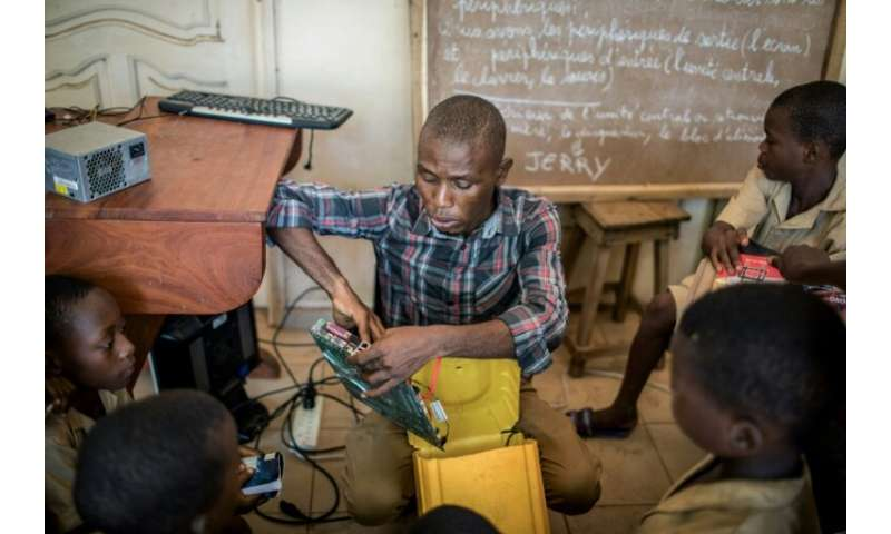 Trainer Raoul Letchede shows the kids the components they will use to assemble a makeshift computer in a 25-litre plastic contai