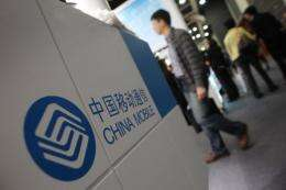 Visitors walk past a stand for China Mobile at the Mobile Asia Congress in Hong Kong
