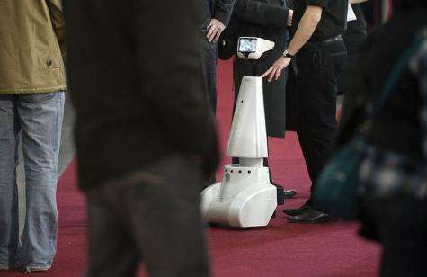 Visitors walk past the robot