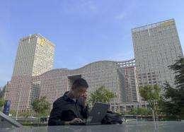 A man surfs the internet in the street in Beijing
