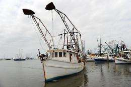 A fiishing boat approaches a dock to make repairs in Pass Christian, Mississippi