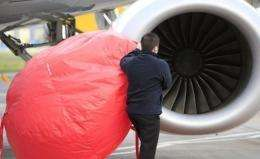 Airport staff secure dust covers on the engines of a passenger aircraft at Belfast City Airport