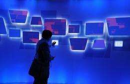 An attendee tries an interactive display at the Microsoft booth at the 2010 International Consumer Electronics Show
