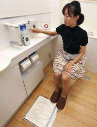 "An employee of Japan's Daiwa House demonstrates the ""Intelligent Toilet"" in Tokyo"