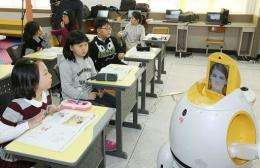 "An English-teaching robot (R), ""Engkey"", stands in front of children at an elementary school in South Korea"