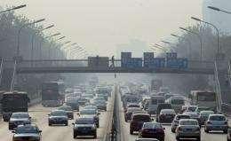 A pedestrian walks across an overpass above traffic on a hazy day in Beijing
