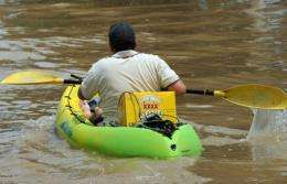 A resident paddles a kayak loaded with XXXX beer back to his flooded home in Rockhampton