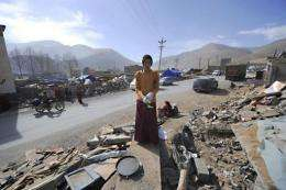 A Tibetan Buddhist monk puts on gloves as he cleans up rubble