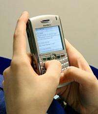 A woman sends text messages on her Blackberry phone