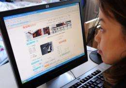 A woman shops online in Beijing as online sales in China rose 22 percent in 2010