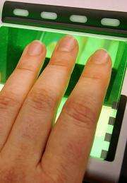 A woman uses a fingerprint scanner